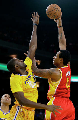 Rockets forward Greg Smith shoots over Festus Ezeli of the Warriors. Photo: Ben Margot