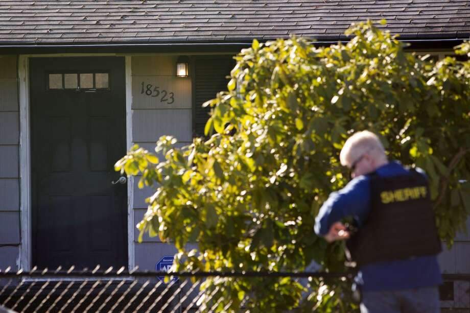 A Shoreline Police sheriff stands outside of a house following a SWAT raid of the premises in search of a suspect in Shoreline.