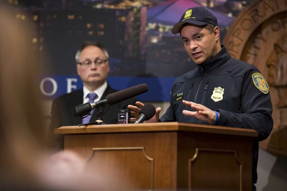 Seattle Police Department Assistant Chief Nick Metz, right, briefs reporters about a shooting that left one man critically injured on Friday, March 8, 2013, at City Hall in Seattle. The suspect, Carolyn Piksa, was arrested in Burien, about three hours after the incident began.