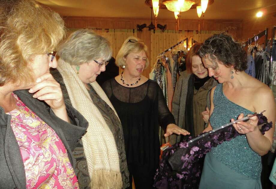 Fairfield fashion designer Jennifer Butler, right, who has a shop at 1326 Post Road, shows one of her dresses at her Friday benefit show to a group of women, from left, Karen Ronald, director of the Fairfield Public Library; Donna Orazio, president of the Friends of the Fairfield Public Library; Erica Green, a member of the board of the Friends of the Fairfield Public Library, and Alexis Sulinski of Derby.  FAIRFIELD CITIZEN, CT 3/8/13 Photo: Meg Barone / Fairfield Citizen freelance