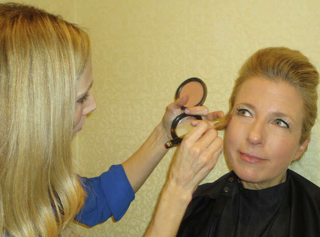Leslie Atiles, owner of Distinct Artistry in Fairfield, applies makeup to Kristin Kolk of Fairfield, one of about a dozen models in Jennifer Butler's annual spring fashion show, held Friday at the Delamar Hotel in Southport, to support the Fairfield Public Library.  FAIRFIELD CITIZEN, CT 3/8/13 Photo: Meg Barone / Fairfield Citizen freelance