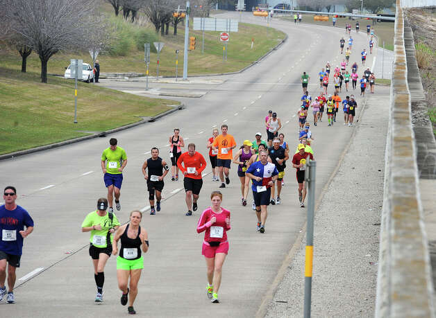 Racers run south on Martin Luther King Parkway during the 2013 Gusher Marathon on Saturday. Photo taken March 09, 2013 Guiseppe Barranco/The Enterprise Photo: Guiseppe Barranco, STAFF PHOTOGRAPHER / The Beaumont Enterprise