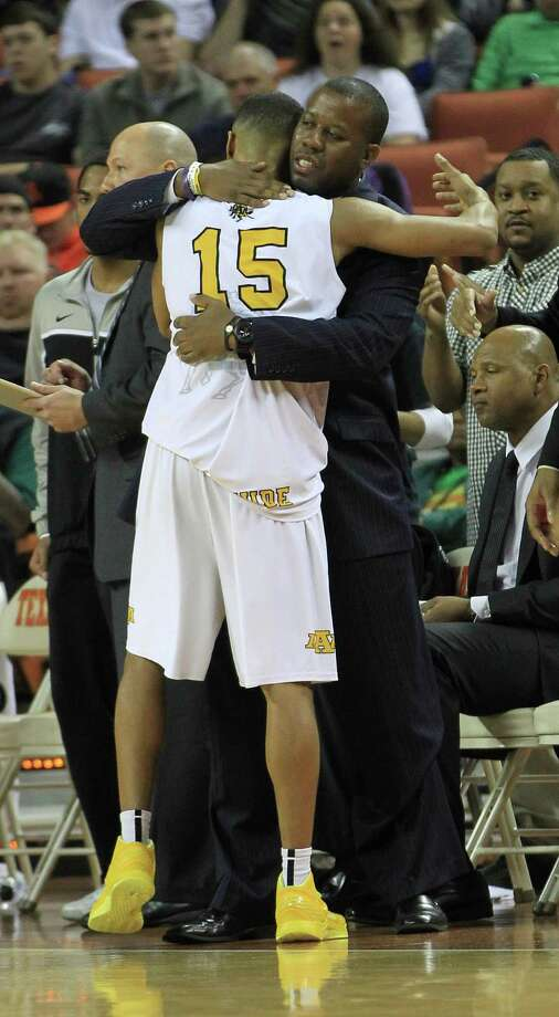 Dallas Triple A Academy's Jeremiah Jefferson (15) hugs a coach after their win in the UIL 1A Division 1 boys state basketball final game between Dallas Triple A Academy and Mumford at the Frank Erwin Center, Saturday, March 9, 2013, in Austin. Photo: Karen Warren, Houston Chronicle / © 2013 Houston Chronicle
