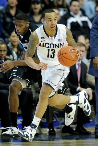 Connecticut's Shabazz Napier, right, is pursued by Providence's Kris Dunn during the second half of Connecticut's 63-59 overtime win in an NCAA college basketball game in Storrs, Conn., Saturday, March 9, 2013. (AP Photo/Fred Beckham) Photo: Fred Beckham, Associated Press / FR153656 AP