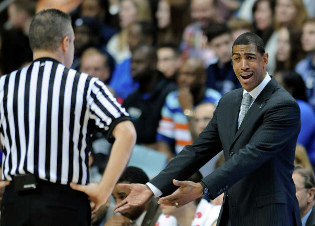 Connecticut coach Kevin Ollie, right, speaks to an official during the first half of his team's 63-59 overtime win against Providence in an NCAA college basketball game in Storrs, Conn., Saturday, March 9, 2013. (AP Photo/Fred Beckham) Photo: Fred Beckham, Associated Press / FR153656 AP