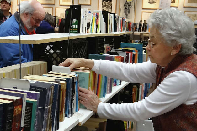 Barbara Licker, one of about 75 volunteers for the four-day book sale at the Westport Public Library, straightens stacks of books  Saturday.  WESTPORT NEWS, CT 3/9/13 Photo: Mike Lauterborn / Westport News contributed