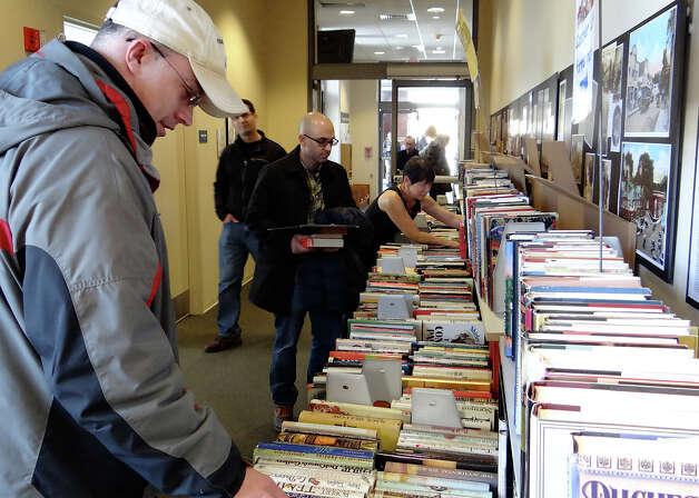 Brent Weaver of Norwalk browses fiction titles on the opening day of Westport Public Library's Winter Book Sale on Saturday.  WESTPORT NEWS, CT 3/9/13 Photo: Mike Lauterborn / Westport News contributed