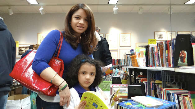 Jenny Echeverria of Greenwich and daughter Nathalia, 5, pick out children's books Saturday at Westport Public Library's Winter Book Sale.  WESTPORT NEWS, CT 3/9/13 Photo: Mike Lauterborn / Westport News contributed
