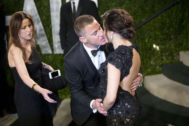 Channing Tatum kissing his wife isn't the awkward one; it's the handler trying to break up some romance. (Vanity Fair Oscar Party, 2013).