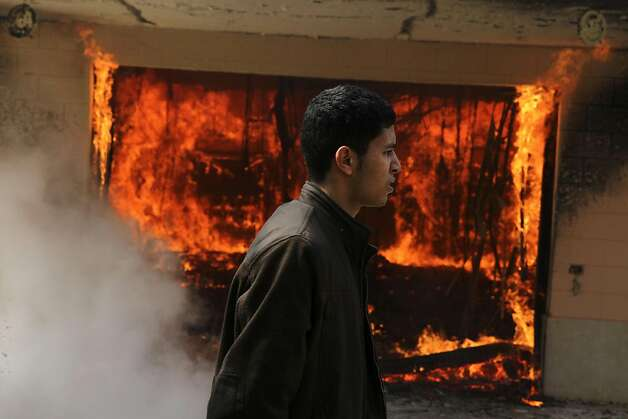 An Egyptian man walks on the grounds of a police officer's club as a fire set by protesters burns in Cairo, Egypt, Saturday, March 9, 2013. An Egyptian court on Saturday confirmed the death sentences against 21 people for taking part in a deadly soccer riot but acquitted seven police officials for their alleged role in the violence, touching off furious protests in Cairo that torched the soccer federation headquarters and a nearby police club.(AP Photo/Ahmed Gomaa) Photo: Ahmed Gomaa, Associated Press