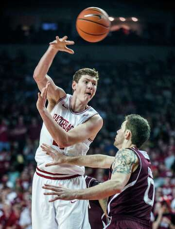Arkansas' Hunter Mickelson, left, makes a pass as Texas A&M's Andrew Young, right, defends during the first half of an NCAA college basketball game in Fayetteville, Ark., Saturday, March 9, 2013. (AP Photo/April L. Brown) Photo: April Brown, Associated Press / FR81294 AP