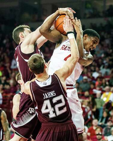 Arkansas' Coty Clarke, right, has a shot attempt blocked by Texas A&M's Andrew Young, back left, as Texas A&M's Jarod Jahns (42) defends during the first half of an NCAA college basketball game in Fayetteville, Ark., Saturday, March 9, 2013. (AP Photo/April L. Brown) Photo: APRIL BROWN, Associated Press / FR81294 AP