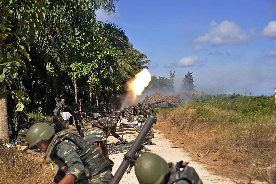 Malaysian soldiers fire mortars to flush out Filipino gunmen who took over a disputed village in the resource-rich Borneo state of Sabah. The standoff has entered its second month. Photo: Associated Press