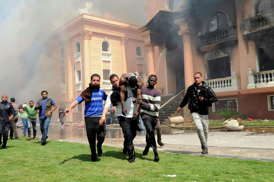 An injured security official is carried from a police officers club in the upscale neighborhood of Zamalek, after protesters set fires following a court verdict in Cairo, Egypt, Saturday, March 9, 2013. Fans of Cairo's Al-Ahly club have stormed Egypt's soccer federation headquarters and a nearby police club, and set them ablaze after a court acquitted seven of nine police official on trial for their alleged part in deadly stadium melee. (AP Photo/Mohammed Asad ) Photo: Mohammed Asad, Associated Press / AP