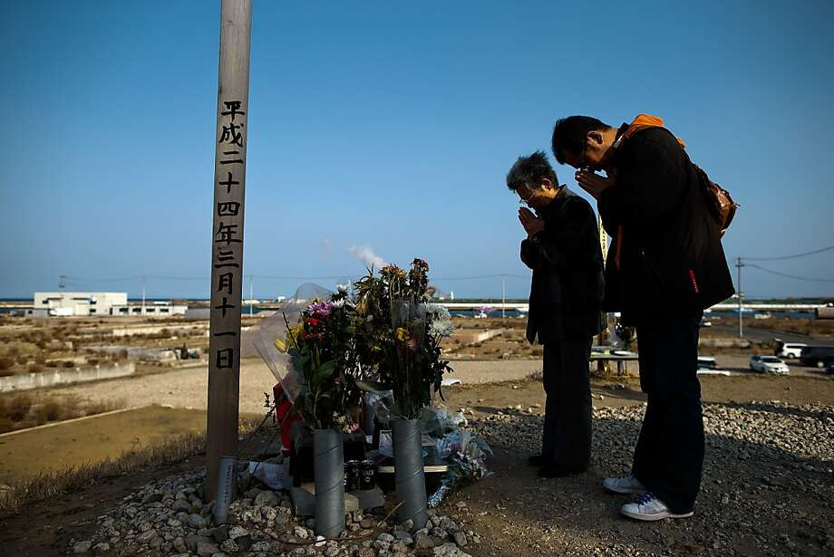 A family in Natori, Japan, pays its respects to victims of the earthquake and tsunami during the second-anniversary commemoration. Photo: Athit Perawongmetha, Getty Images