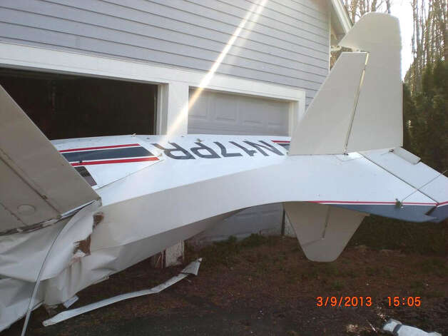 An airplane is seen on its side partially into a house between Woodinville and Duvall. (Photo courtesy King County Sherrif's Office)