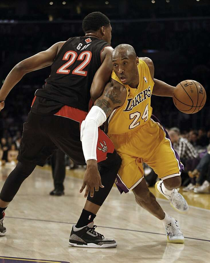 A focused Kobe Bryant drives hard against Rudy Gay (22) of the Toronto Raptors during first-half action in Friday's home game that the Lakers won in OT. Photo: Gary Friedman, McClatchy-Tribune News Service