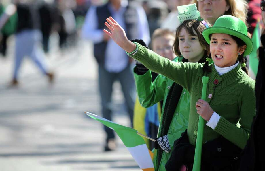 Nine-year-olds Alexa Iannuccilli, of Milford, left, and Ana Rodriguez, of Woodbridge, wave to the marchers during the annual St. Patrick's Day Parade in downtown Milford, Conn. Saturday, Mar. 9, 2013. Photo: Autumn Driscoll / Connecticut Post