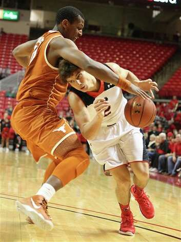 Texas Tech's Dusty Hannahs, right, drives against Texas' Jonathan Holmes during their NCAA college basketball game in Lubbock, Texas, Saturday, March 9, 2013. (AP Photo/Lubbock Avalanche-Journal, Zach Long)  ALL LOCAL TV OUT Photo: Zach Long, Associated Press / Lubbock Avalanche-Journal