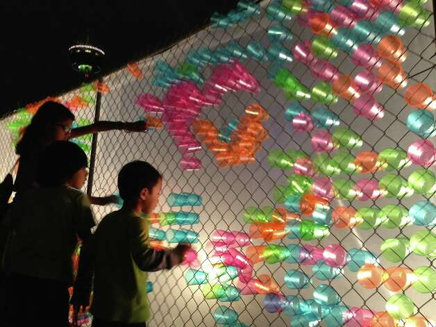 Kids play with the Lite-Brite fence next to the Magik Children's Theatre during Luminaria on Saturday, March 9, 2013. Photo: Benjamin Olivo / MySA.com