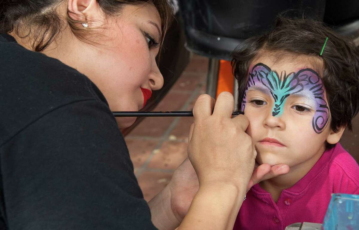 4 year-old Wren Cooper, daughter of George Cooper of San Antonio gets her face painted by Pamela Godz during the S.M.A.R.T. (Supporting Multiple Arts Resources Together) third annual Pie to the People at the historic La Villita March 9, 2013.