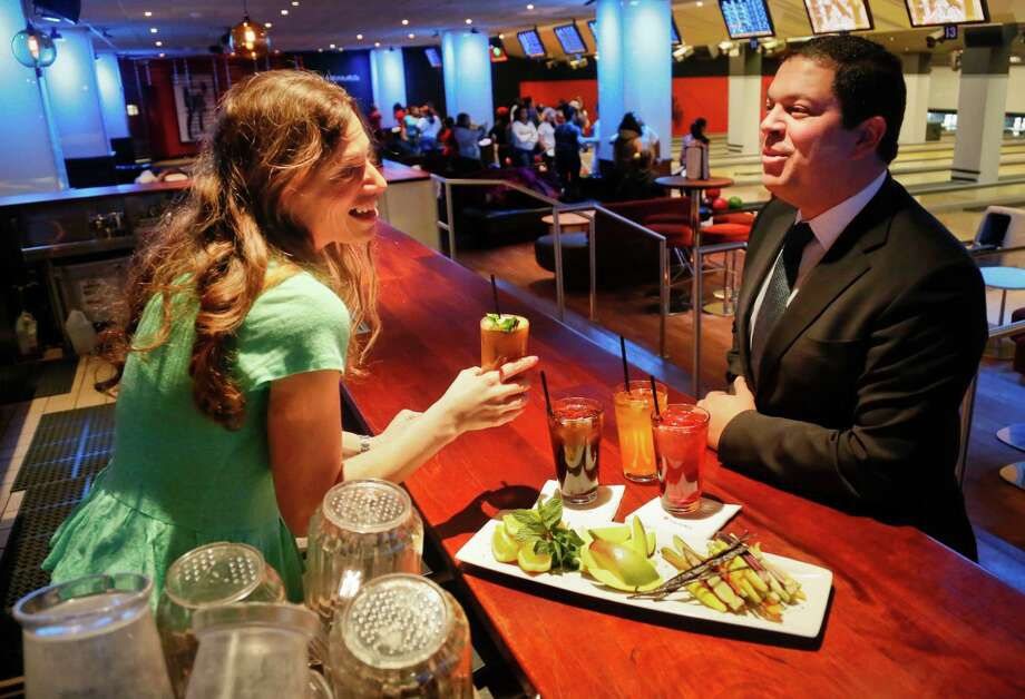 Ayman Kamel, right, executive general manager of Frames Bowling Lounge, and Frayda Resnick, marketing coordinator at Frames, pose with a display of 16-ounce drinks, including fruits for a new natural mix, on Friday, March 8, 2013, in New York.  In preparation for the nation's first limit on the size of sugar-laden beverages, set to take effect Tuesday, families who pack the lanes on weekends will no longer be offered pitchers of soda, Kamel said. Instead, they will promote healthy drink options mixing carrot, beet and mint-and-citrus and eight-ounce cups of soda.  (AP Photo/Bebeto Matthews) Photo: Bebeto Matthews