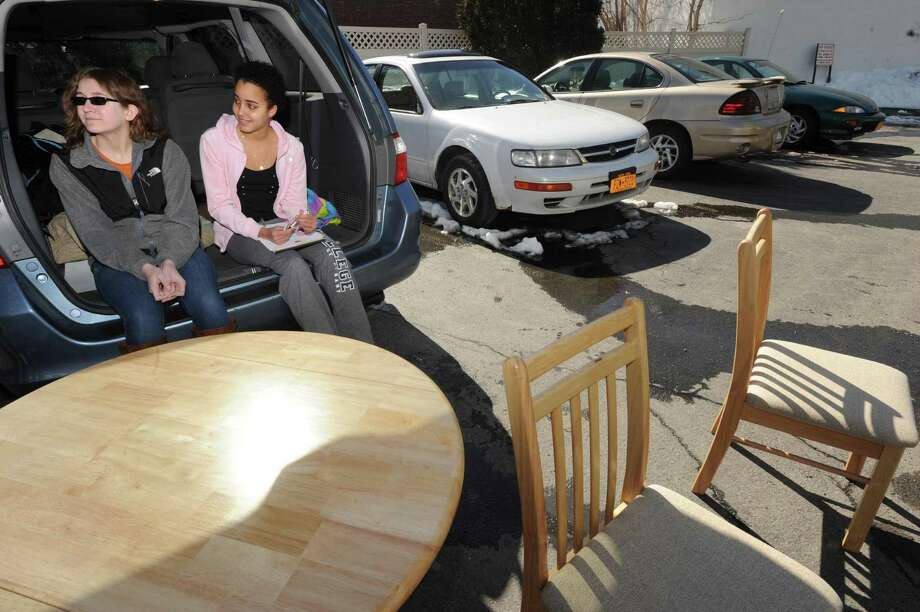 Bethlehem High School student Olivia Harmon, left, and HVCC student Yulie Carrazana-Markman with a table a chair donated to senior Ronald Orr at the Westview Apartments  on Saturday March 9, 2013 in Albany, N.Y. (Michael P. Farrell/Times Union) Photo: Michael P. Farrell