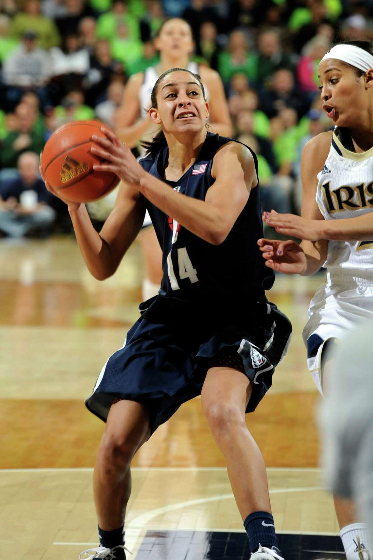 Connecticut guard Bria Hartley, left, heads up court as Notre Dame guard Skylar Diggins defends during action in a college basketball game Monday March 4, 2013 in South Bend, Ind. (AP Photo/Joe Raymond)