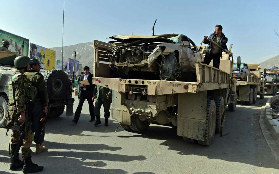 Afghanistan National Army soldiers remove a car that was destroyed in the suicide bomber's attack next to the Afghan Defense Ministry. Photo: Massoud Hossaini / Getty Images