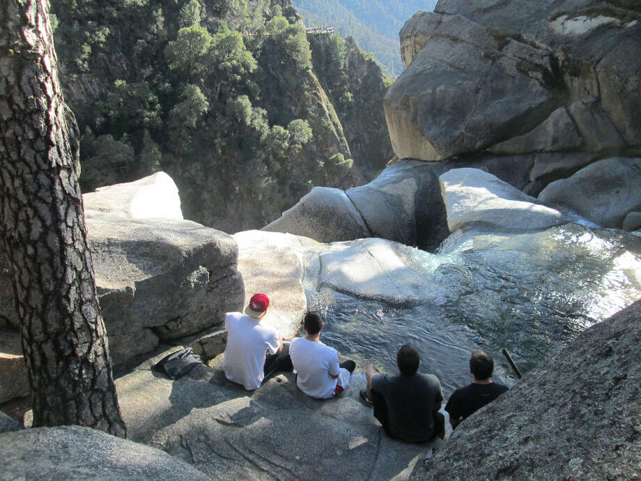Up above the brink of the falls, a group of four Chico State students watch the water go by