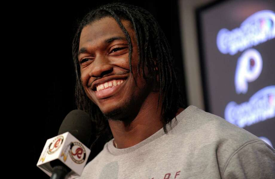 FILE - In this Jan. 2, 2013, file photo, Washington Redskins quarterback Robert Griffin III smiles as he speaks during a news conference following an NFL football practice at Redskins Park in Ashburn, Va. Griffin has won The Associated Press 2012 NFL Offensive Rookie of the Year award, beating out two other sensational first-year quarterbacks, it was announced on Saturday, Feb. 2, 1013. (AP Photo/Susan Walsh, File) Photo: Susan Walsh, Associated Press / AP