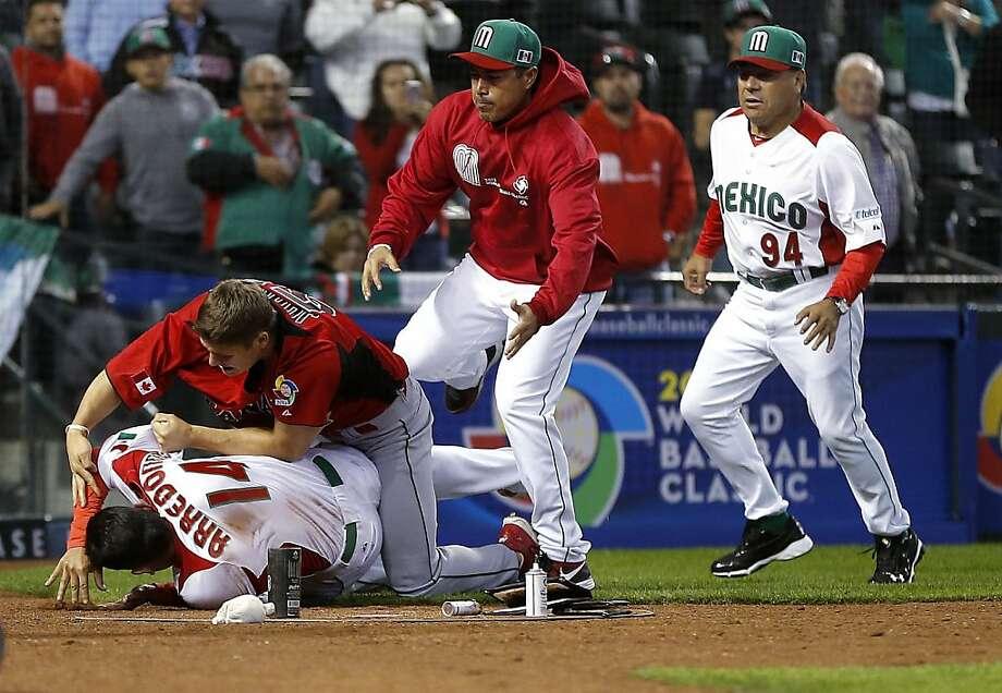 Canada's Jay Johnson tackles Mexico's Eduardo Arredondo during the brawl. Photo: Matt York, Associated Press