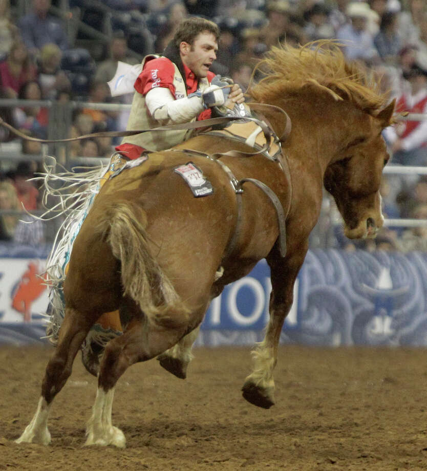 Casey Colletti works to hold himself up after his hand stuck in rigging after his ride in bareback event during the Super Shootout at RodeoHouston in Reliant Stadium Saturday, March 9, 2013, in Houston. Photo: Melissa Phillip, Houston Chronicle / © 2013  Houston Chronicle