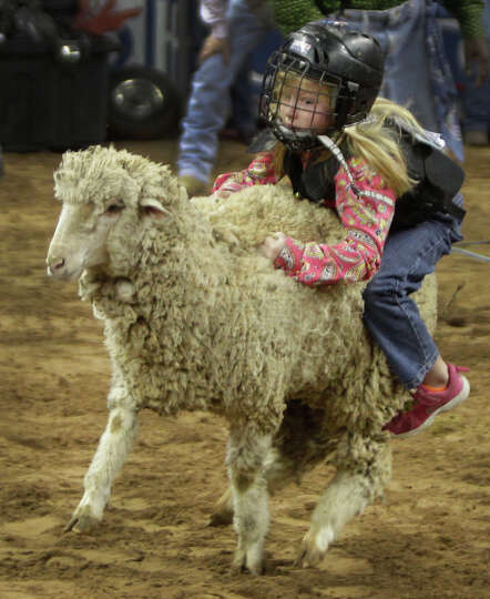 Kate Chandler, 6,  of Houston works to hang during Mutton Bustin' event at RodeoHouston in Reliant S