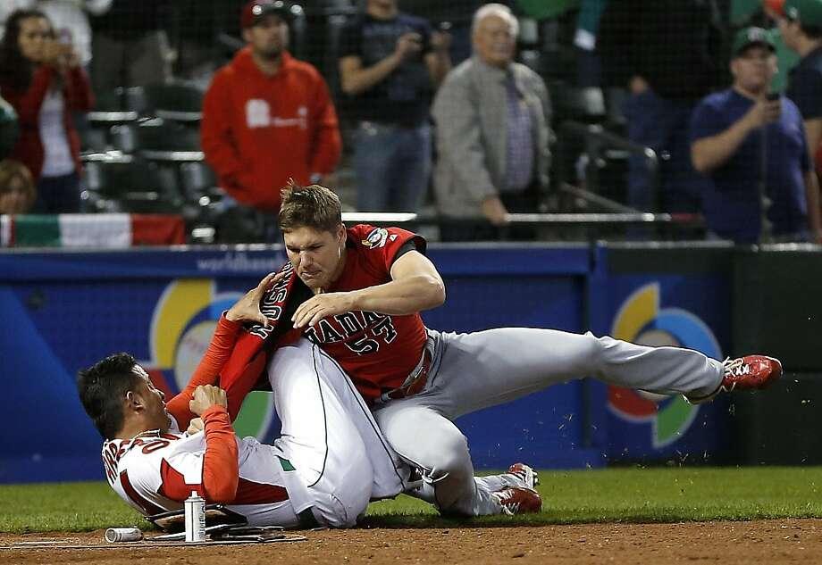 Canada's Jay Johnson, right, and Mexico's Eduardo Arredondo fight during the ninth inning of a World Baseball Classic game, Saturday, March 9, 2013, in Phoenix. (AP Photo/Matt York) Photo: Matt York, Associated Press