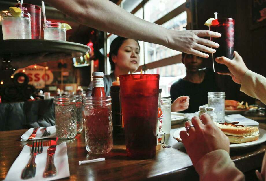 Come Tuesday, the 24-ounce glass (center) containing a sugary drink will be illegal in New York City. The 16-oz. glass on the right represents the max size. Photo: Photos By Bebeto Matthews / Associated Press