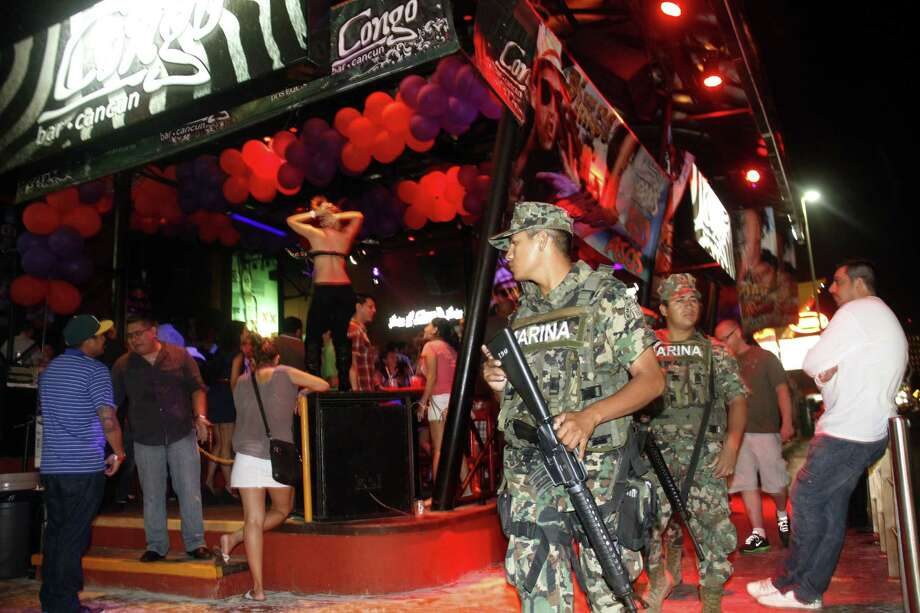 Mexican navy marines patrol the nightclub section of Cancún as Spring Break revelers do their thing. The resort city remains a favorite destination despite warnings about potential violence. Photo: Israel Leal / Associated Press