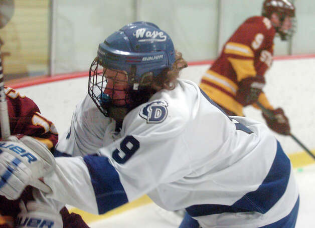 Darien's Dana Wensberg puts a player into the boards as Darien and St. Joseph High Schools face off in the Division 1 Boys Hockey quarterfinals at Terry Connors Ice Rink in Stamford, Conn., March 9, 2013. Photo: Keelin Daly / Keelin Daly