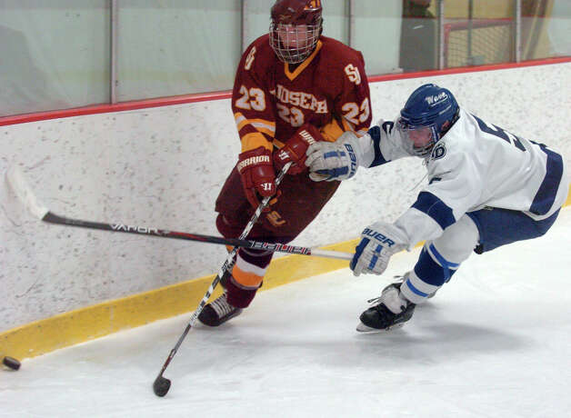 Darien's Owen Koorbusch and St. Joseph's Sean Smith in action as Darien and St. Joseph High Schools face off in the Division 1 Boys Hockey quarterfinals at Terry Connors Ice Rink in Stamford, Conn., March 9, 2013. Photo: Keelin Daly / Keelin Daly