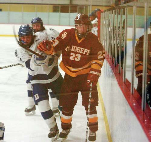 Darien's Jack Knowlton and St. Joseph's Sean Smith batttle as Darien and St. Joseph High Schools face off in the Division 1 Boys Hockey quarterfinals at Terry Connors Ice Rink in Stamford, Conn., March 9, 2013. Photo: Keelin Daly / Keelin Daly