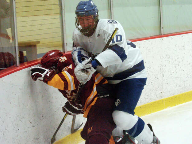 Darien's Jack Massie and St. Joseph's Matt Greenhut battle along the boards as Darien and St. Joseph High Schools face off in the Division 1 Boys Hockey quarterfinals at Terry Connors Ice Rink in Stamford, Conn., March 9, 2013. Photo: Keelin Daly / Keelin Daly
