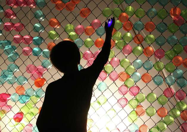 A boy plays with illuminated cups against a fence behind the Magik Children's Theatre during Luminaria on Saturday, March 9, 2013. Photo: Susana Hayward / For The San Antonio Express-News