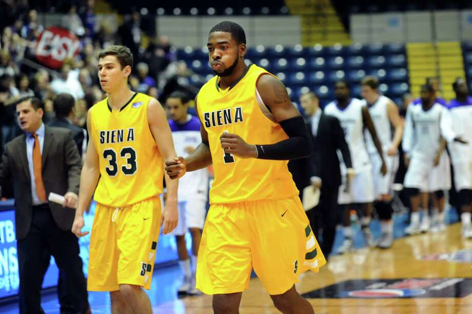 Siena's O.D. Anosike (1), center, and Rob Poole (33) walk off the court after they lost to Niagara 74-62 in their quarterfinal MAAC Championship basketball game on Saturday, March 9, 2013, at MassMutual Center in Springfield, Mass. (Cindy Schultz / Times Union) Photo: Cindy Schultz / 10021492A