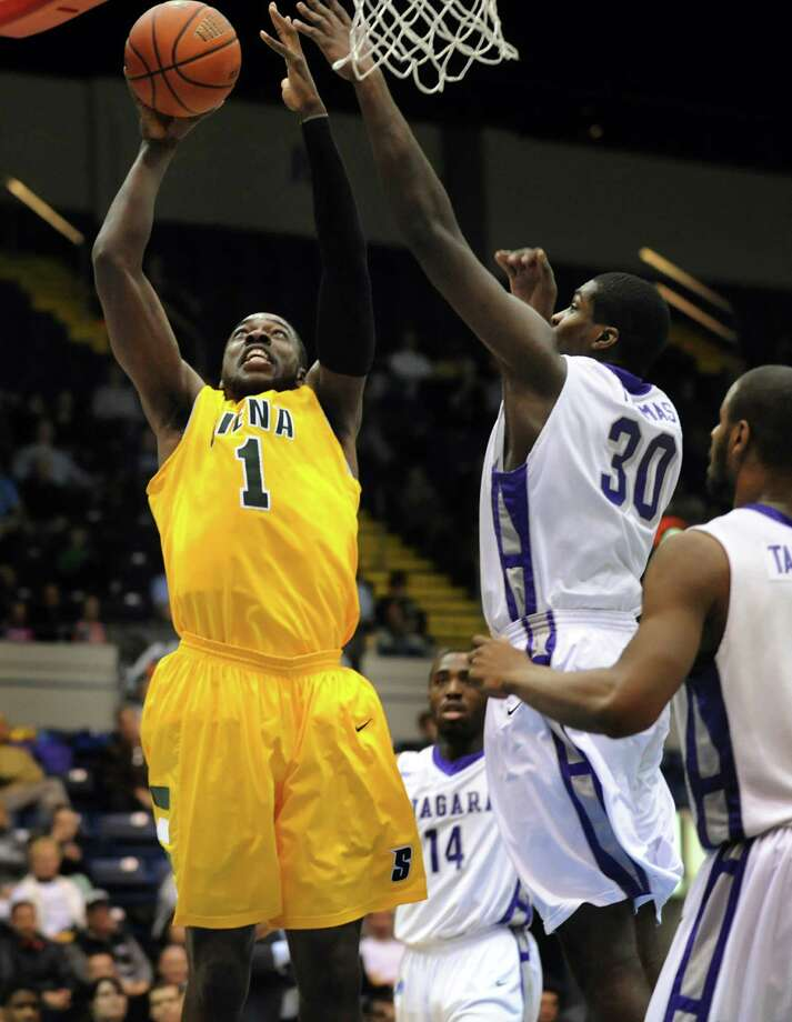 Siena's O.D. Anosike (1), left, shoots for two points as Niagara's Joe Thomas (30) defends in their quarterfinal MAAC Championship basketball game on Saturday, March 9, 2013, at MassMutual Center in Springfield, Mass. (Cindy Schultz / Times Union) Photo: Cindy Schultz / 10021492A