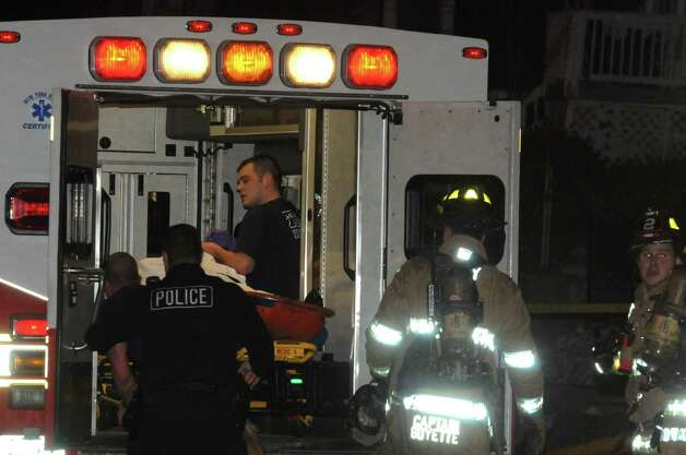 Emergency personnel in Troy bring a fire victim to the ambulance after a blaze hit a house in the 500 block of Fourth Street, near Lincoln. (Photo by IPA)