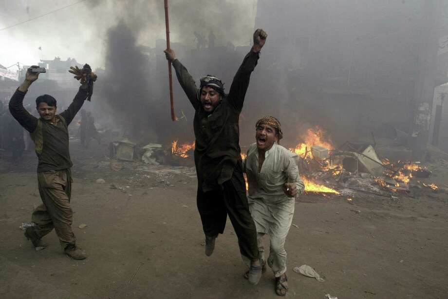 Pakistani men, part of an angry mob, react after burning belongings of Christian families in Lahore. Muslim protesters turned violent over derogatory remarks allegedly made by a Christian against Prophet Muhammad. Photo: K.M. Chaudary / Associated Press