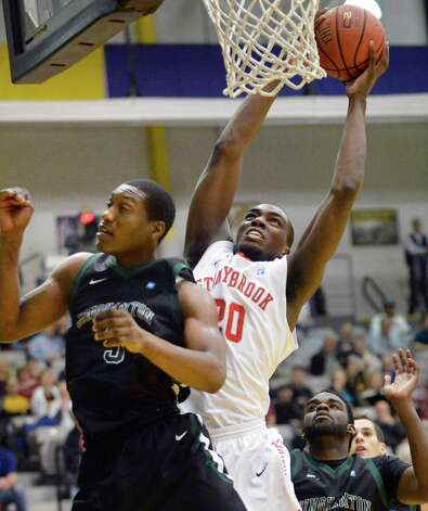 Stony Brook's #20 Jameel Warney dunks past Binghamton's #3 Jordan Reed, left, during their America East tournament game Saturday March 9, 2013. (John Carl D'Annibale / Times Union) Photo: John Carl D'Annibale / 10021442A