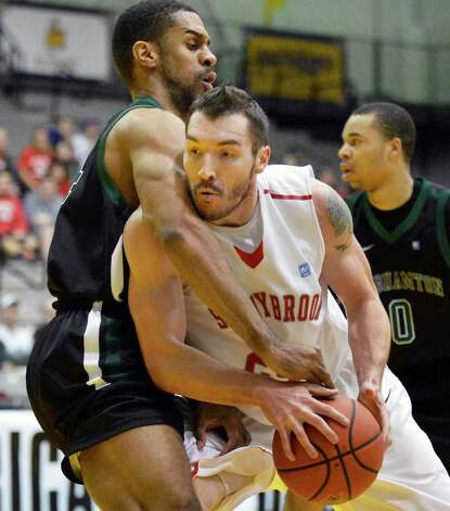 Stony Brook's #24Tommy Brenton muscles his way away from Binghamton's #14 Brian Freeman, left, during their America East tournament game Saturday March 9, 2013. (John Carl D'Annibale / Times Union) Photo: John Carl D'Annibale / 10021442A