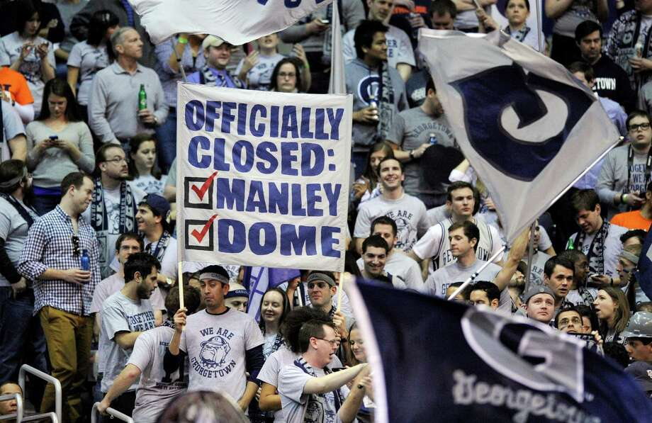 Georgetown fans hold up signs during the first half of an NCAA college basketball game between Georgetown and Syracuse, Saturday, March 9, 2013, in Washington. (AP Photo/Nick Wass) Photo: Nick Wass