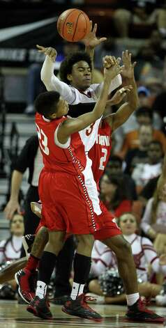 South Grand Prairie's Mark Howell (3) battles for a rebound against Travis' Tyronne Jordan (23) and Aaron Harrison (2) during the first half of the UIL 5A boys state basketball championship game between Fort Bend Travis and South Grand Prairie at the Frank Erwin Center, Saturday, March 9, 2013, in Austin. Photo: Karen Warren, Houston Chronicle / © 2013 Houston Chronicle